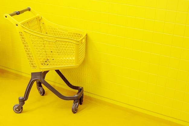 買い物のコンセプトです。黄色の床の上に空の黄色の食料品のカートが立っています