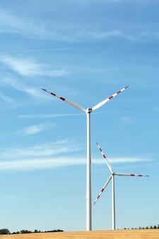 Взгляд ветроэнергетической установки на предпосылке голубого неба и полей с зерновыми культурами.