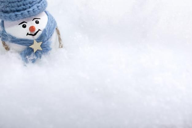 青い帽子とスカーフの小さな雪だるまが雪の吹きだまりの中に立っています。