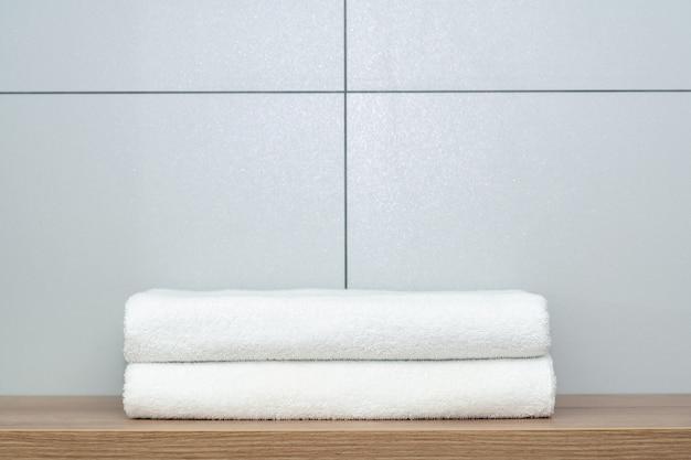Два аккуратно сложенных белых полотенца лежат на деревянной полке на фоне керамической плитки.