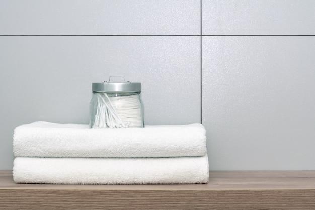 Два белых полотенца аккуратно сложены лежат на деревянной полке, на вершине которой стоит банка с ватными дисками и ушными палочками на керамической плитке.
