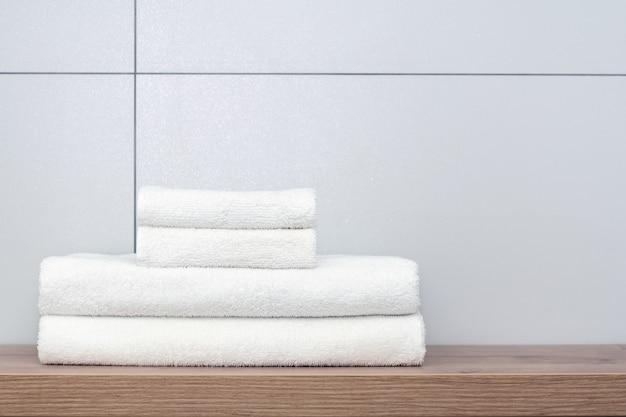 Два больших и два маленьких аккуратно сложенных белых полотенца лежат на деревянной полке на фоне керамической плитки.