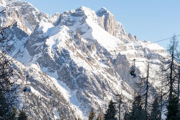 冬。人々は、雪をかぶった山々に囲まれたスキーリフトにチェアリフトを登ります。スキー、風景の概念。
