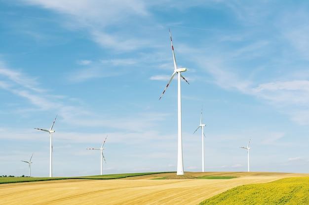 青い空と穀物作物のフィールドの背景に風力発電所のビュー。