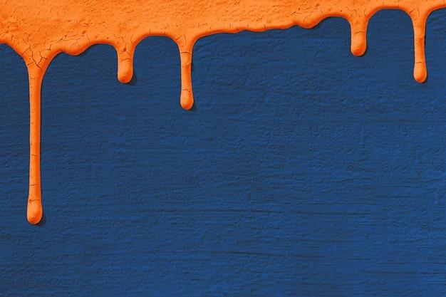Фон с текстурой бетонной штукатуркой стены в синий, на котором падает оранжевый цвет стекает вниз. концепция текстуры, ремонт, цвет