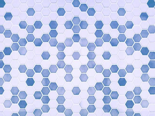 Фон светло-голубой и белой керамической плитки в форме шестиугольника, который покрывает стену в виде мозаики. концепция текстуры,