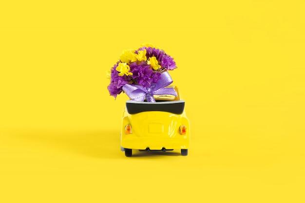 黄色の小さな黄色い車の中にある紫色の花のカラフルな花束の眺め。セレクティブフォーカス。休日、結婚式、花配達、ギフトの概念