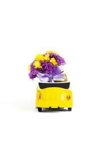 小さな黄色い車の中にある紫色の花のカラフルな花束の眺め。セレクティブフォーカス。休日、結婚式、花配達、ギフトの概念