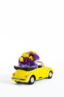 小さな黄色のレトロな車の中にある紫色の花のカラフルな花束の眺め。セレクティブフォーカス。休日、結婚式、花配達、ギフトの概念