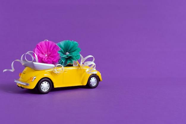 花が紫の上に横たわる小さな明るいオレンジ色の車の眺め。