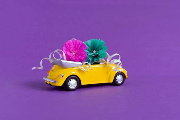 花が紫の上に横たわる小さなカラフルな黄色の車の眺め。