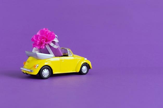 Взгляд малого красочного желтого автомобиля в котором подарочная коробка с смычком на пурпуре. концепция праздника, транспорт, день святого валентина, игрушки