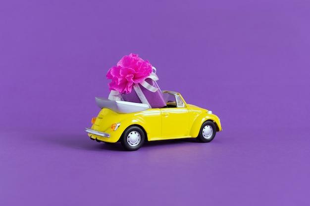 Взгляд малого красочного желтого автомобиля в котором подарочная коробка с смычком на пурпуре. концепция праздника, транспорт, день святого валентина, доставка