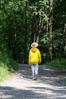 Девушка в ярко-желтой толстовке с капюшоном идет по тропинке в лесу.