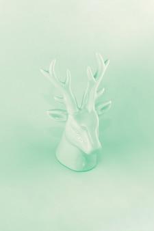 ネオミント色のクリスマス鹿の彫刻の眺め。冬の休暇の概念、ミニマリズム、抽象化、今年の色。