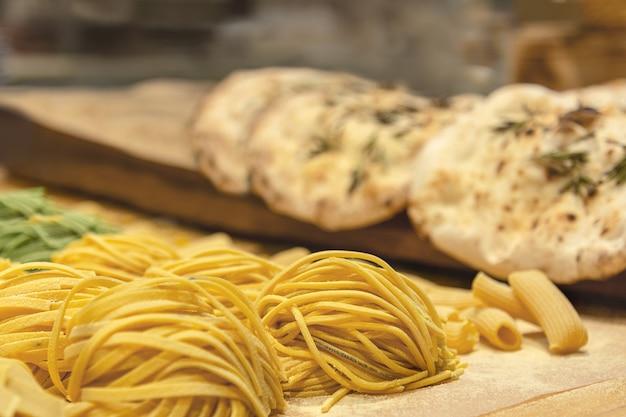 新鮮な自家製小麦パスタはチアバットを背景にテーブルの上に重ねられます。