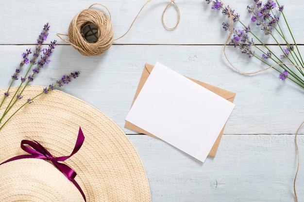 ヴィンテージ麦わら帽子、クラフト紙の封筒、手紙、麻ひも、素朴な青い木製の机の上のラベンダーの花