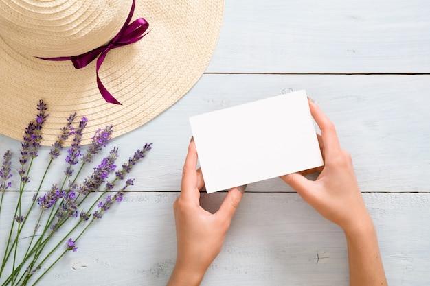 Руки женщины, держащей пустую белую карточку