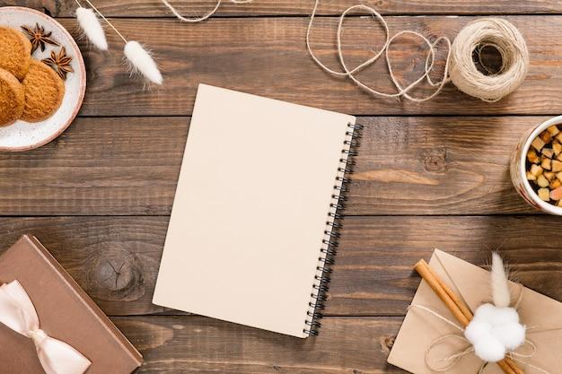 クラフト紙のメモ帳、ロープ、お茶、クッキー、ギフトボックス、ヴィンテージの封筒とワークスペース。