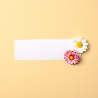 色とりどりの花とパステルイエローの背景の空白の紙ラベルで作られた春の組成物。