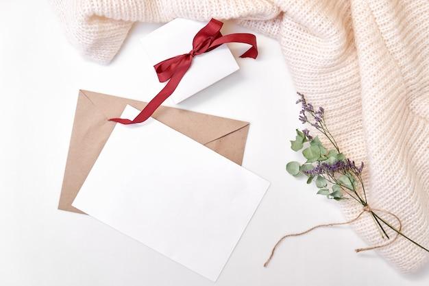 クラフト封筒、空白の紙、弓のギフトボックス、ニットスカーフ、ドライフラワーと葉