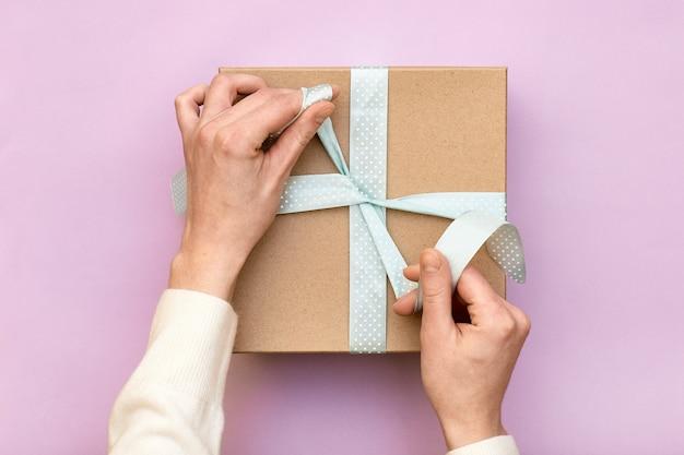 Женщина руки, держа ремесло подарочной коробке с синим бантом на пастельных розовом фоне