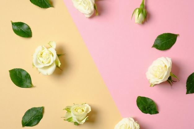 パステルピンクと黄色の背景にバラの葉とバラの花で作られたフレームの枠線。