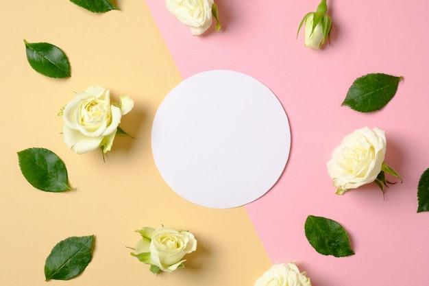 散在する葉とバラの花とパステルピンクと黄色の背景の空白の白い円形の紙。