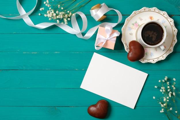 Концепция свадебного утра. пригласительный билет, шоколад в форме сердца, подарочная коробка, чашка кофе, цветы.