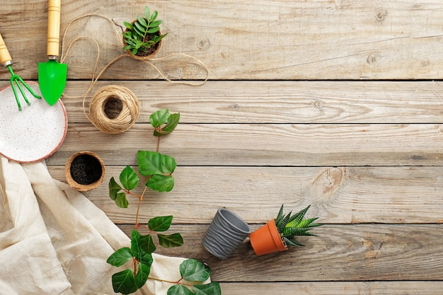 園芸工具およびヴィンテージの木製の机の上の花。