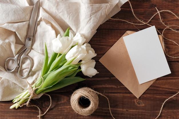 白いチューリップの花、空白の紙カード、はさみ、素朴な木製の机の上のひもの春の花束。