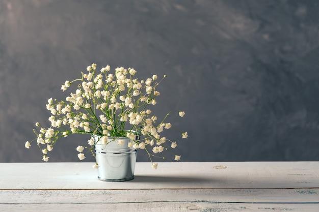 木製のテーブルの上の金属製のバケツで新鮮な春の花のアレンジメント