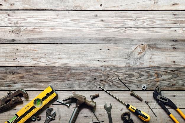 木製の背景に大工のさまざまなツールとトップビューワークベンチ