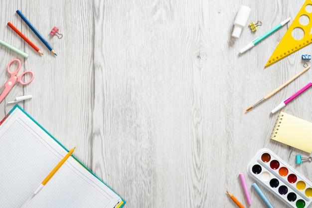 学校のノートと木製の背景にさまざまな供給。学校概念に戻る。