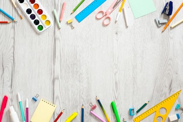 学校概念に戻る、木製の背景にさまざまな学用品と創造的なレイアウト
