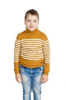 Мальчик в джинсах и полосатом свитере на белом фоне