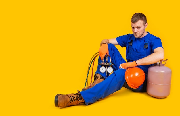 Унылый уволенный работник при шлем безопасности сидя на желтой стене. мужчину в комбинезоне уволили с работы. концепция экономического кризиса, безработицы и производства