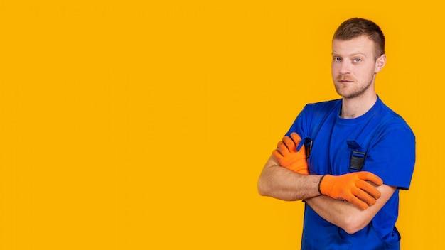 Молодой работник мужского пола в перчатках и комбинезонах