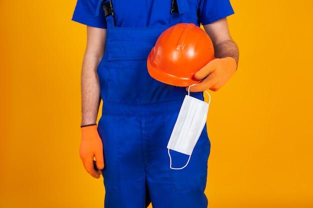 建設のオーバーオールと黄色の背景に手袋の労働者は、彼の手に保護用のヘルメットと医療マスクを保持しています。経済危機、失業生産、コロナウイルスの概念