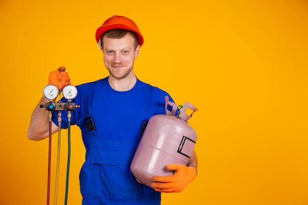 空調技術者。エアコン修理と圧力計、エアコンを充填するための機器。