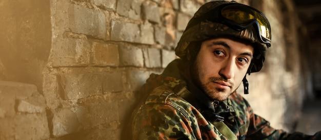 Мужчина военный в шлеме и камуфляжной одежде. задумчивый солдат отдыхает от военной операции. расположение руин