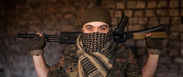 Арабский солдат в головном уборе из национальной куфии с оружием в руках