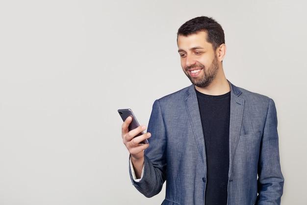 メッセージを読んで手にスマートフォンを持っている男性の起業家の肖像画