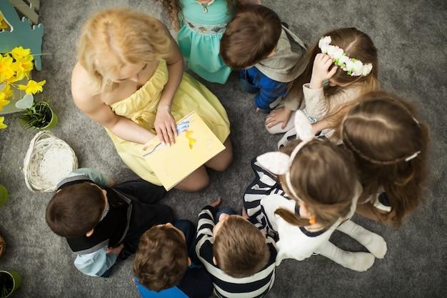 先生は子供たちに本を読んでいます