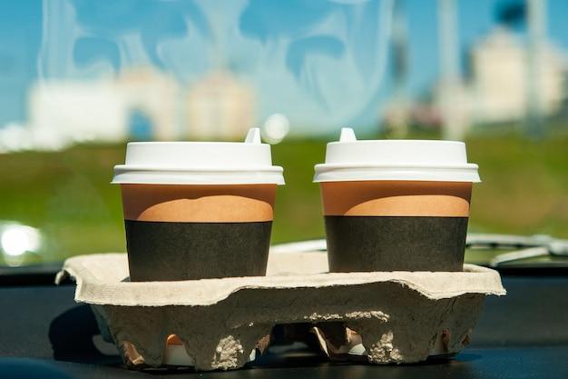 車のパネルの上にコーヒーとカップ