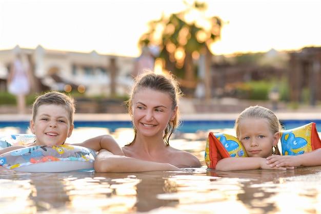 スイミングプールで子供たちと家族のお母さん