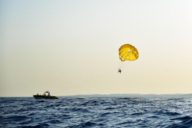 海のエンターテインメントの人々は日没で海の上をパラシュート