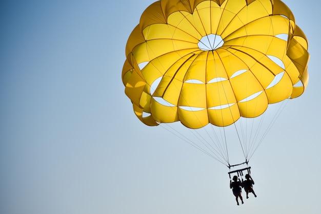 恋人たちのペアが日没で海の上をパラシュートで飛ぶ