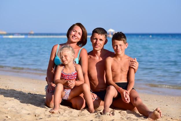 Счастливая семья с двумя детьми на пляже