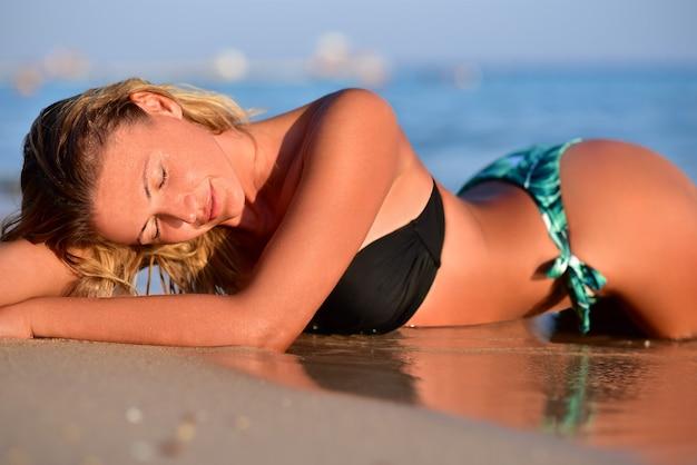 水着のセクシーな女性はビーチに横たわっています。